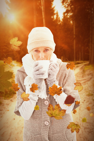 warm clothing: Woman in warm clothing holding mugs against autumn scene