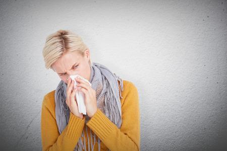 nariz: Cerca de la mujer que sopla su nariz contra la pared gris Foto de archivo