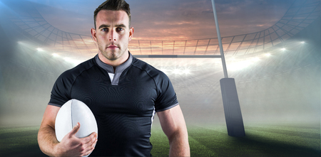 world sport event: Tough rugby player holding ball against rugby stadium