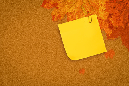 inscribe: Sticky note with grey paperclip against autumn leaves pattern
