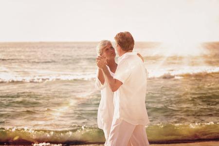 retirement happy man: Light beam against retired couple dancing on the beach
