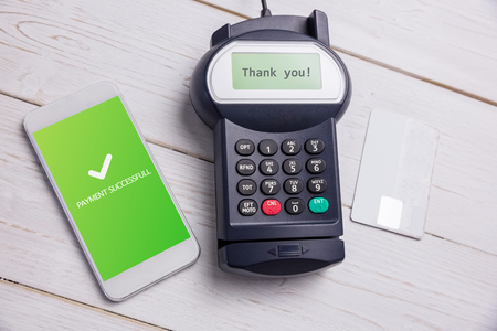retail equipment: Screen showing payment successful with tick against paying with smartphone Stock Photo