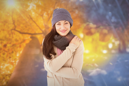 changing clothes: Attractive brunette looking at camera wearing warm clothes against autumn changing to winter