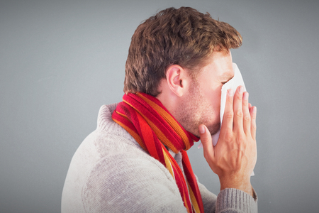 blowing nose: Man blowing nose on tissue against grey background