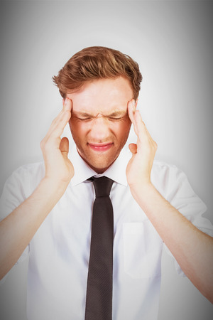 pounding head: Young businessman getting a headache against grey vignette