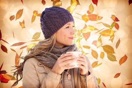 femme blonde: Jolie blonde avec la tasse contre le motif de feuille d'automne dans des tons chauds Banque d'images