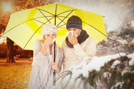realtionship: Couple sneezing in tissue while standing under umbrella against trees and meadow in the park Stock Photo