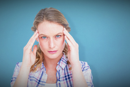 wincing: Pretty hipster with headache  against blue background Stock Photo