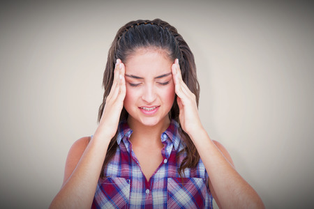 wincing: Upset woman suffering from headache against grey background with vignette Stock Photo