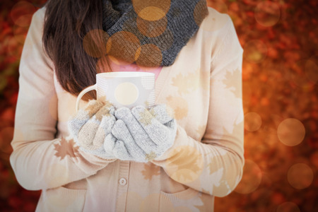 polka dotted: Woman holding polka dotted mug against peaceful autumn scene in forest