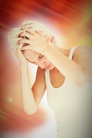 desolaci�n: Sad blonde woman with head pain holding her head  against autumn scene Foto de archivo