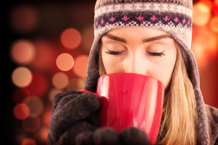 fair woman: Happy blonde in winter clothes holding mug against light circles on black background