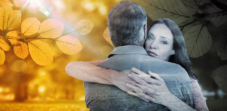desolaci�n: Pares ocasionales abraz�ndose unos a otros contra la escena del oto�o Foto de archivo