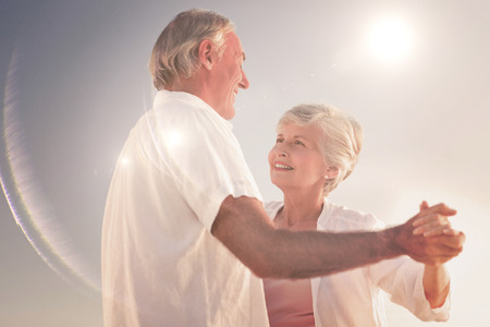 mature couple: Senior couple dancing on the beach against light beam