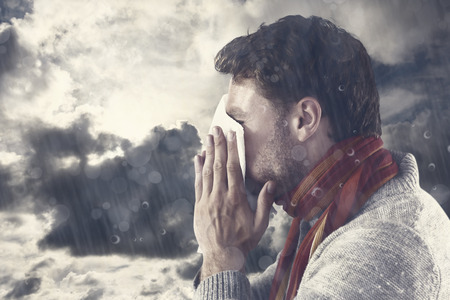 blowing nose: Man blowing nose on tissue against blue sky with white clouds Stock Photo