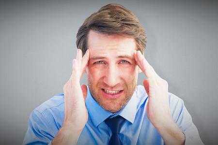 wincing: Young businessman with severe headache against grey background
