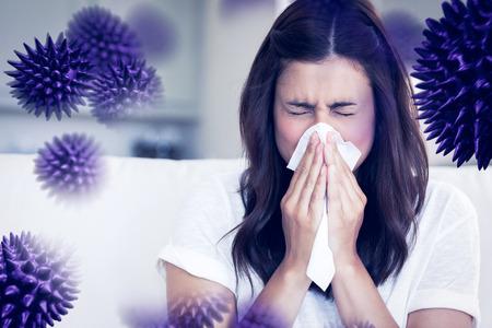 Morena estornudar en un pañuelo de papel contra el virus Foto de archivo