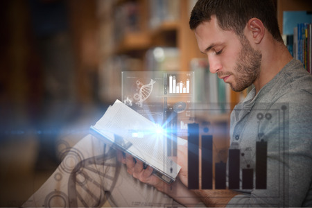 Digital representation of pie chart against serious male student reading a book Stock Photo