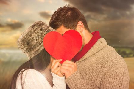 novios besandose: Joven pareja bes�ndose detr�s de coraz�n rojo contra escena de pa�s