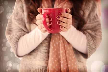 Frau im Winterkleidung mit einem heißen Getränk gegen herbstlichen Blattmuster