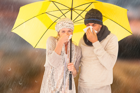realtionship: Couple sneezing in tissue while standing under umbrella against country scene