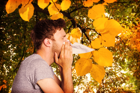 blowing nose: Close up side view of man blowing nose against autumnal leaves against plants Stock Photo