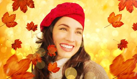 gente adulta: Smiling brunette against yellow abstract light spot design Foto de archivo