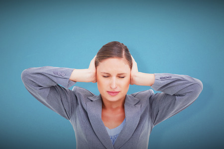 tradeswoman: Close up of annoyed tradeswoman covering her ears against blue background