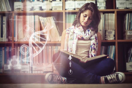 woman looking down: Illustration of DNA against female student against bookshelf reading a book on the library floor Stock Photo