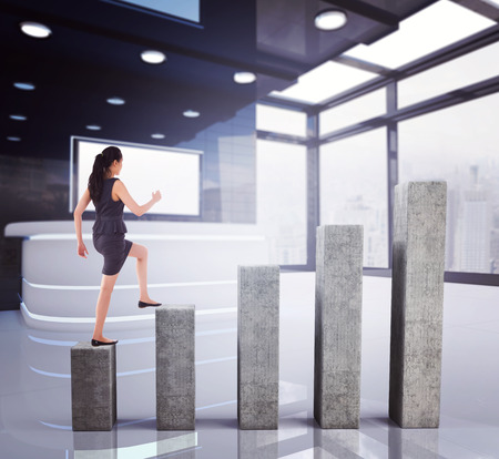 step well: Businesswoman stepping up against bar chart depicting growth Stock Photo