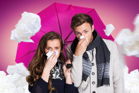blowing nose: Couple blowing nose while holding umbrella against pink vignette