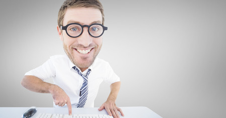 geeky: Geeky businessman typing against grey vignette Stock Photo