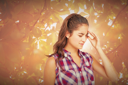 wincing: A pretty brunette with headache  against autumn scene