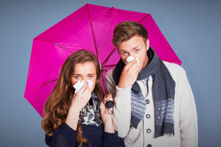 blowing nose: Couple blowing nose while holding umbrella against blue background Stock Photo