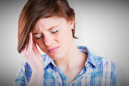 wincing: Pretty brunette getting a headache against grey vignette Stock Photo