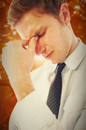 pounding head: Businessman with a headache against autumn scene