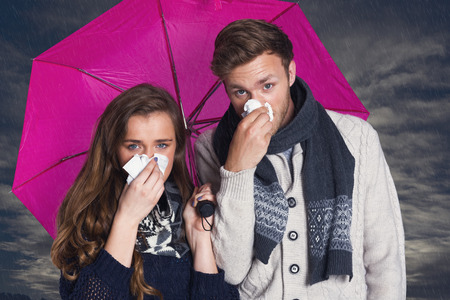 blowing nose: Couple blowing nose while holding umbrella against cloudy sky