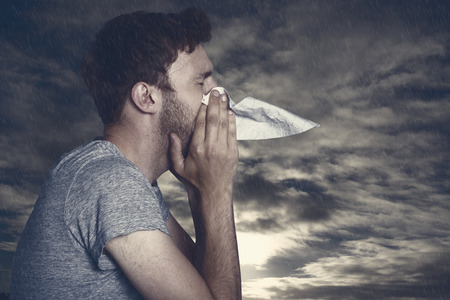blowing nose: Close up side view of man blowing nose against cloudy sky
