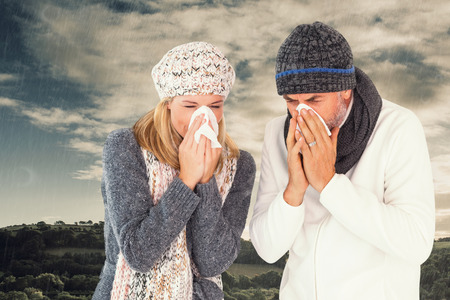 mid adult couple: Couple sneezing in tissue against cloudy sky over countryside