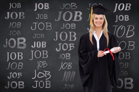academic robe: Smiling blonde student in graduate robe holding her diploma against blackboard