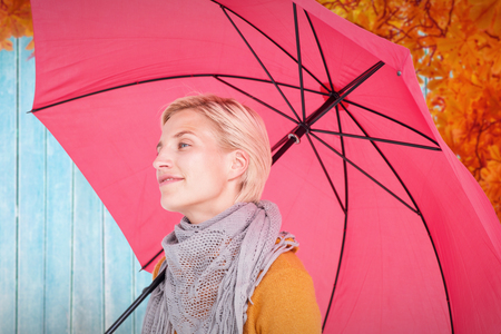 shivering: Happy woman keeping dry against autumn leaves pattern