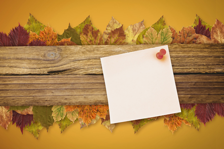 yellow pushpin: Digital image of pushpin on yellow paper  against autumn leaves pattern