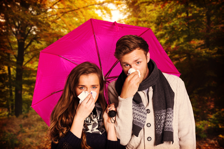 blowing nose: Couple blowing nose while holding umbrella against scenic shot of narrow road along forest