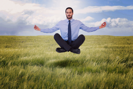lotus pose: Businessman in suit sitting in lotus pose against nature scene Stock Photo