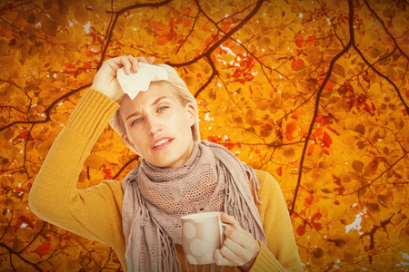 feeling up: Close up of woman feeling her forehead against autumn scene