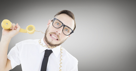 phone cord: Geeky businessman being strangled by phone cord against grey vignette
