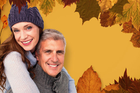 warm clothing: Happy couple in warm clothing against autumn leaves pattern Stock Photo
