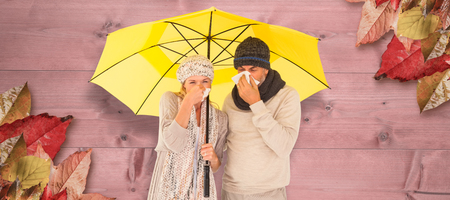 realtionship: Couple sneezing in tissue while standing under umbrella against bleached wooden planks background