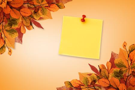 yellow pushpin: Illustrative image of pushpin on yellow paper  against autumn leaves pattern