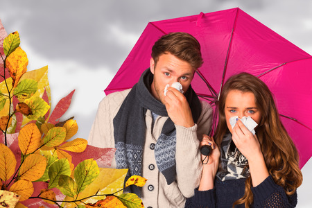 blowing nose: Couple blowing nose while holding umbrella against grey cloudy sky